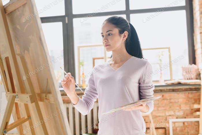 Beautiful Woman Painting in Art Studio