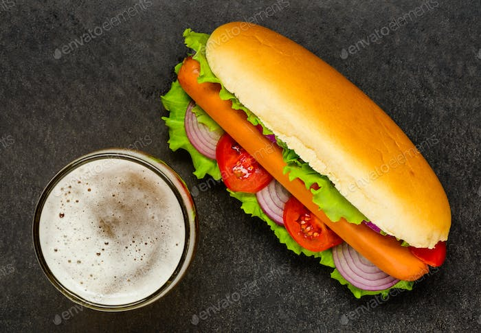 Top View of Hot Dog with Glass Beer on Dark Background