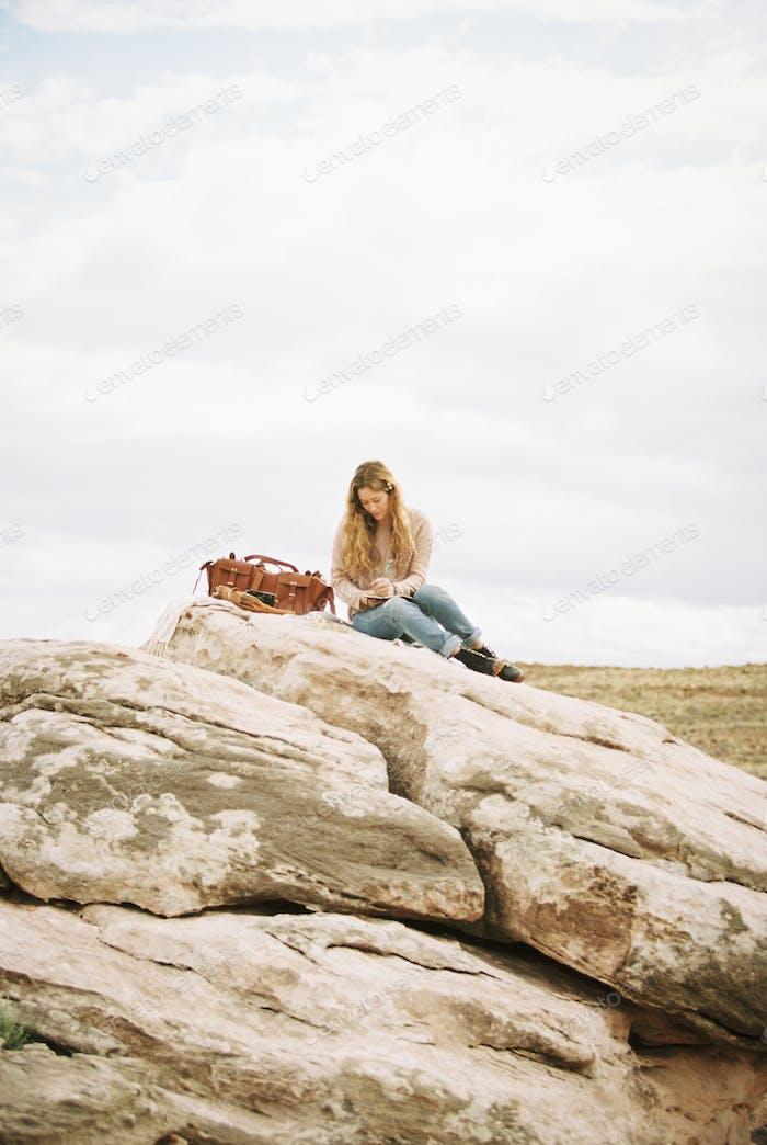 Frau sitzt auf einem Felsen eine Ledertasche neben ihr.