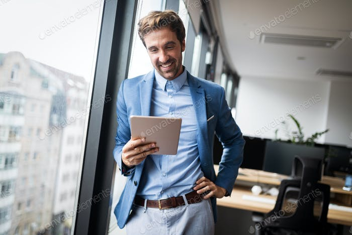 Portrait of young businessman smiling while using digital tablet in office