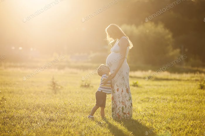 Small boy kissing belly of his pregnant mother outdoors