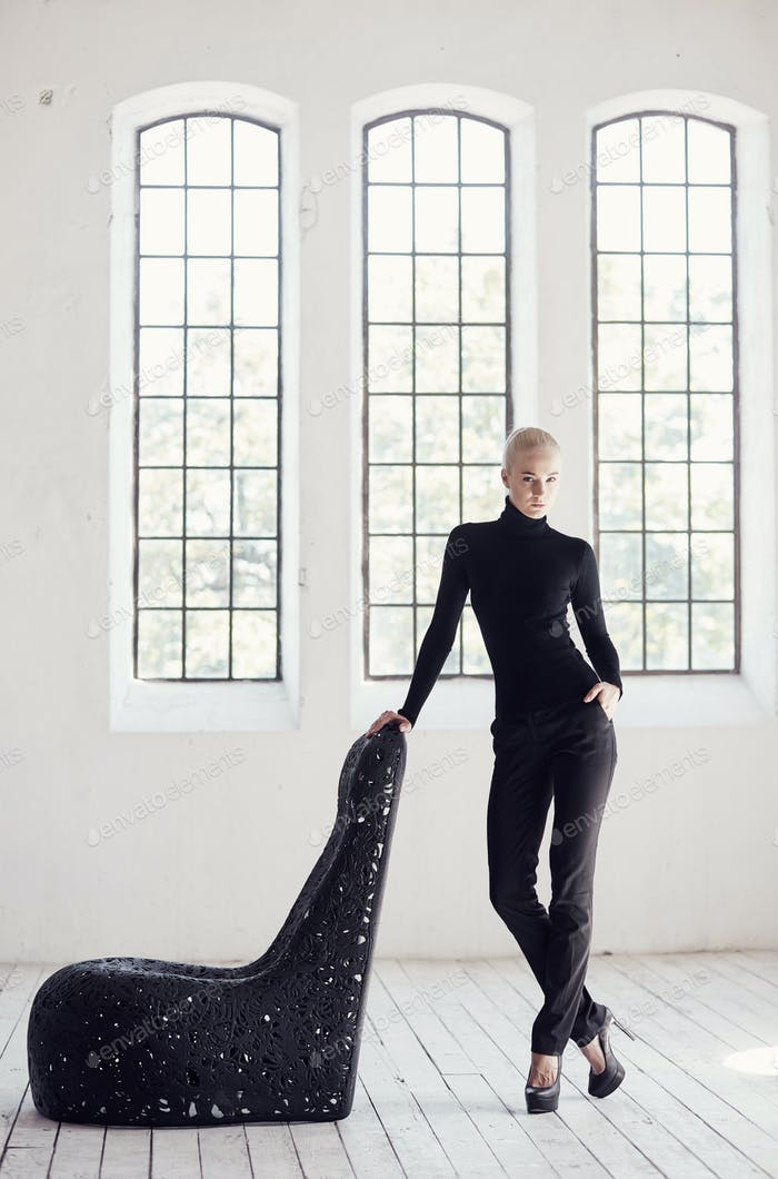 Female posing near artistic black chair.