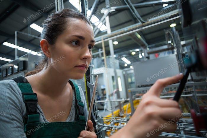 Female factory worker operating machine