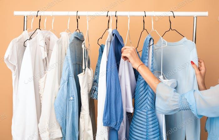 Unerkennbare Frau Wahl Kleidung stehen in der Nähe von Rack