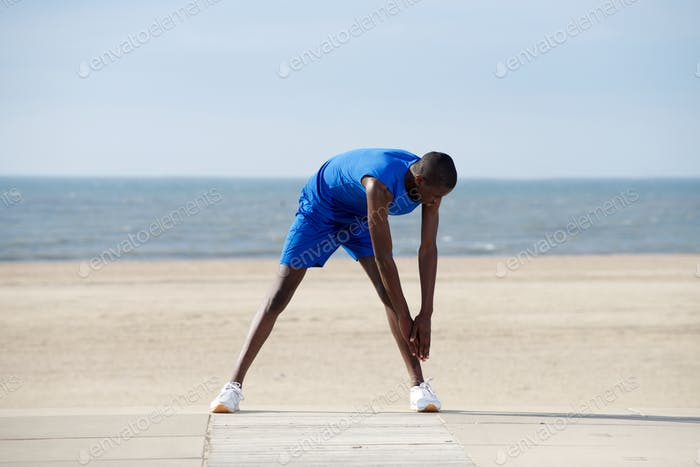Young african american man stretching on the beach