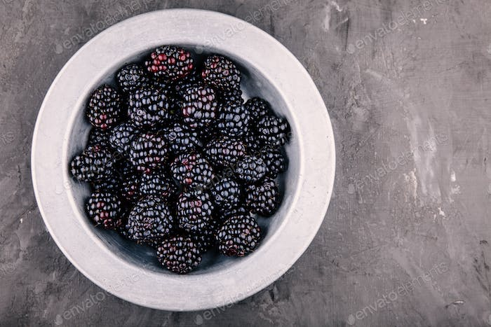 fresh ripe organic blackberries in a bowl on a wooden background