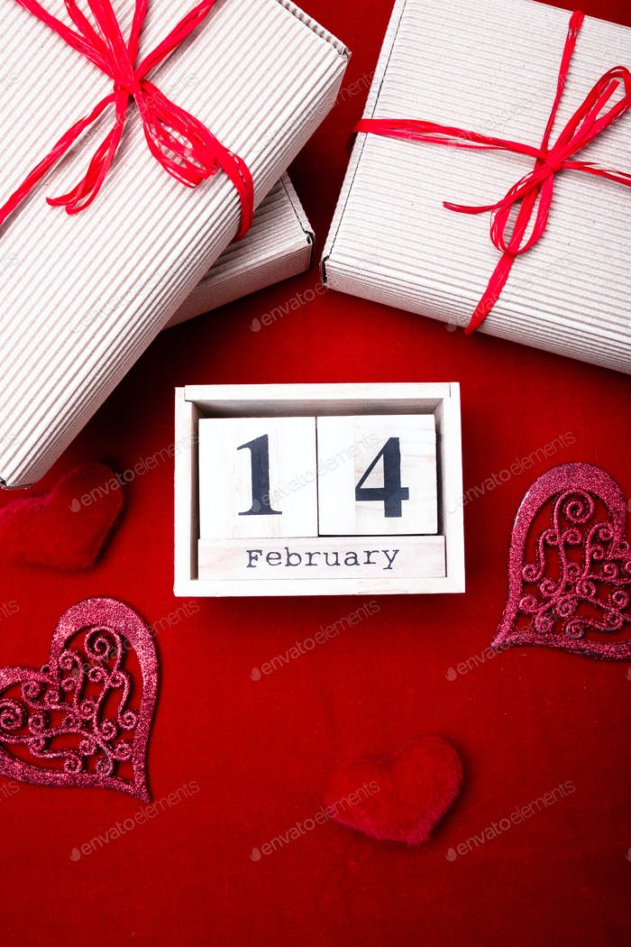 Wooden calendar show of February 14 with red heart and gift boxes.