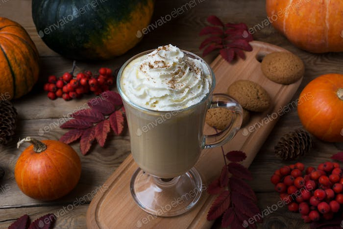 Pumpkin spice coffee latte with whipped cream and cookies