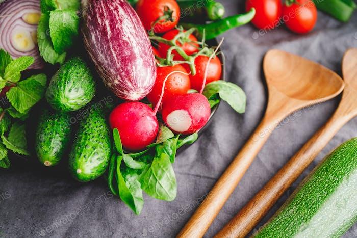 Verschiedene frisches buntes Gemüse in einem Teller auf einem Tisch mit hölzernen Küchenutensilien.