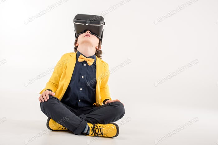 Kid in virtual reality headset sitting on grey