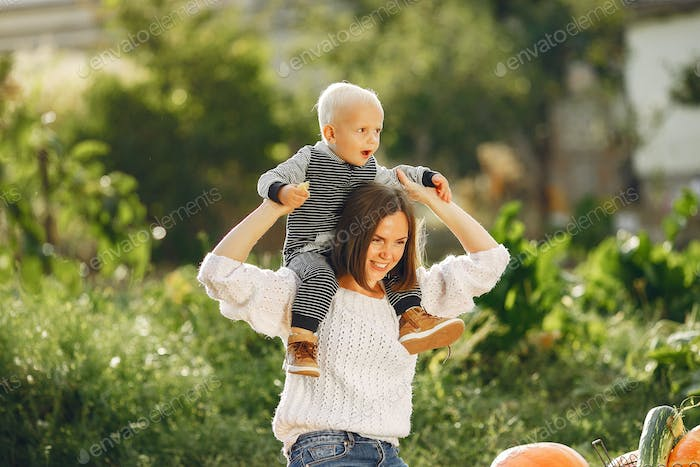 Mother and son sitting on a garden near many pumpkins