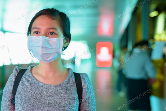 Young Asian woman with mask for protection from corona virus outbreak at the footbridge with blue