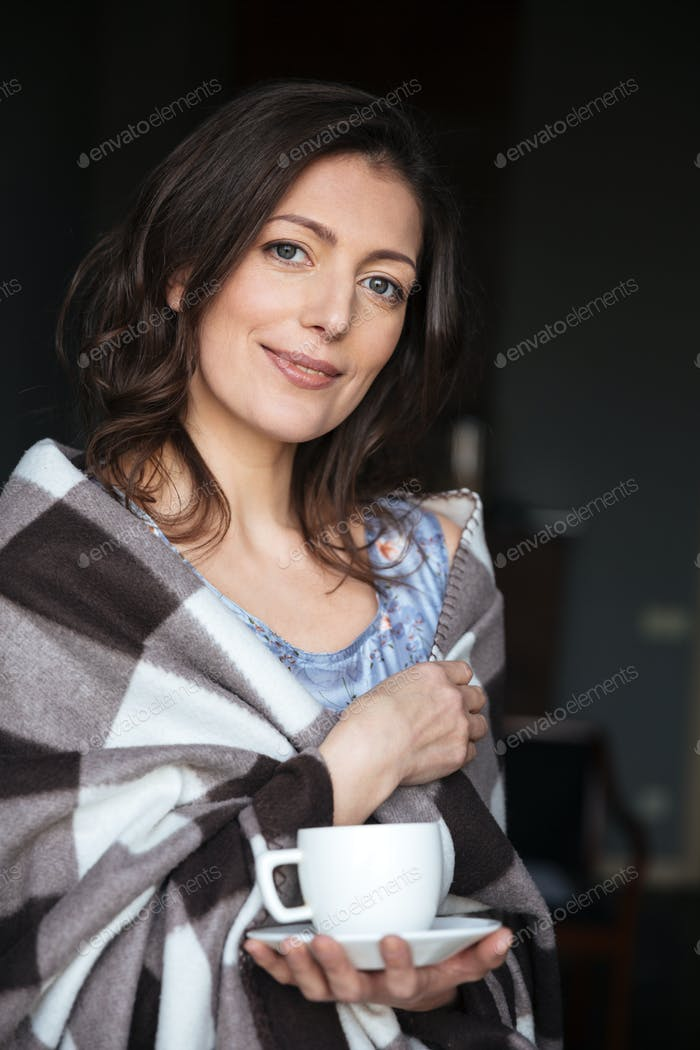 Smiling woman in plaid standing indoors while drinking coffee