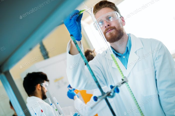 Handsome student of chemistry working with chemicals