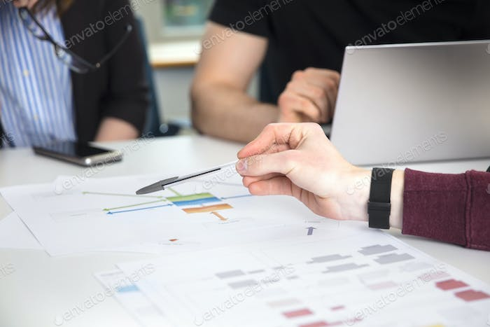 Businessman's Hand Pointing On Chart On Desk