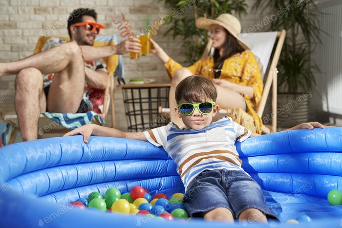 Portrait of boy in swimming pool and parents drinking drink