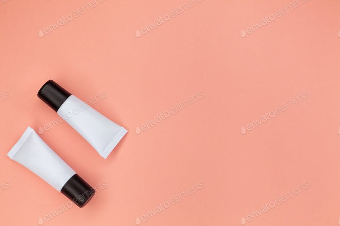 Tubes with cosmetics on a pink background