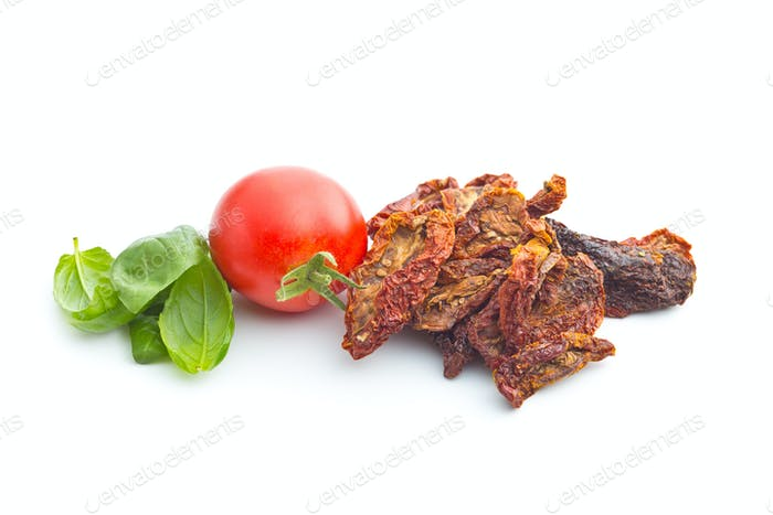 Dried sliced tomatoes and fresh tomatoes with basil leaves.