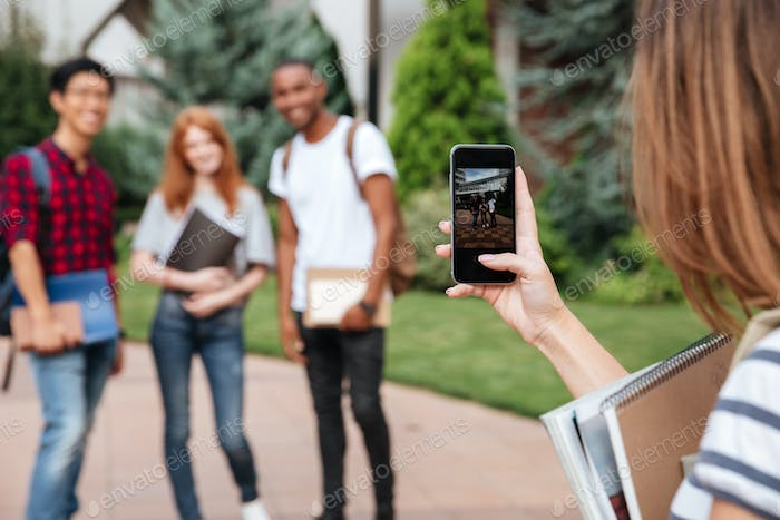 Woman student taking pictures of friends with mobile phone outdoors