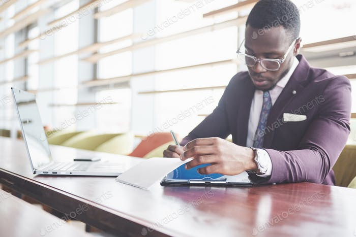 A young businessman signs a contract in a conference room