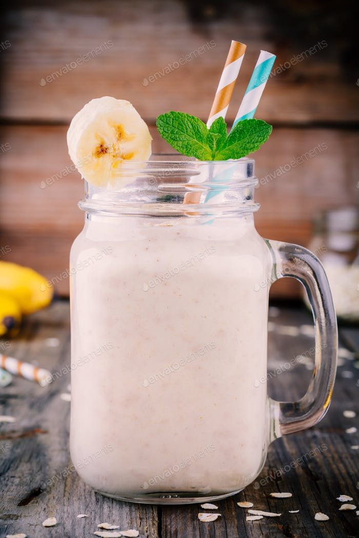 banana smoothie with oatmeal in mason jar on a wooden background