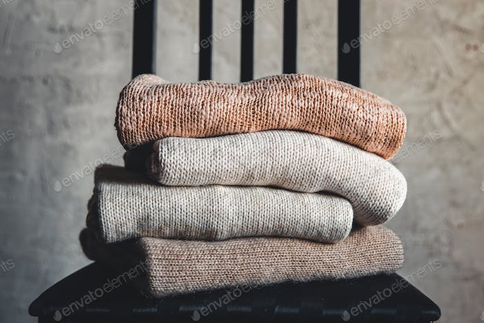 Chair with a stack of knitted sweaters on a gray background. Autumn, Winter concept