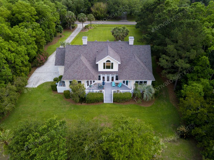 Aerial view of large home with new roof on wooded grassy propert