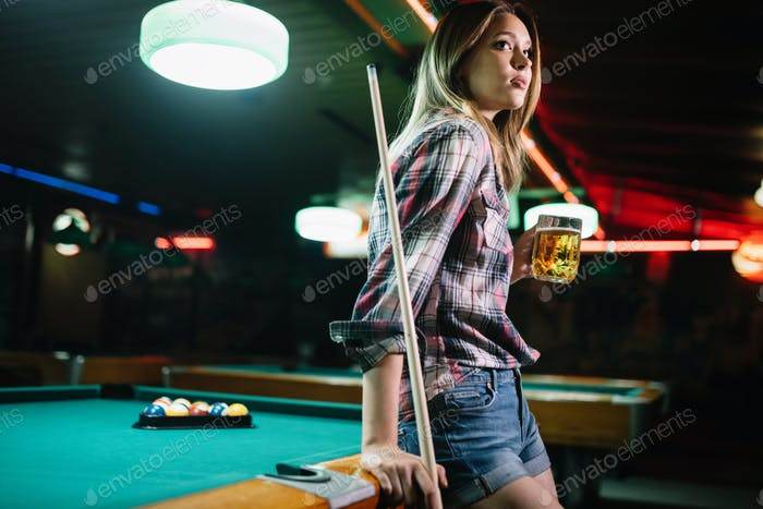 Young smiling girl playing billiard in club