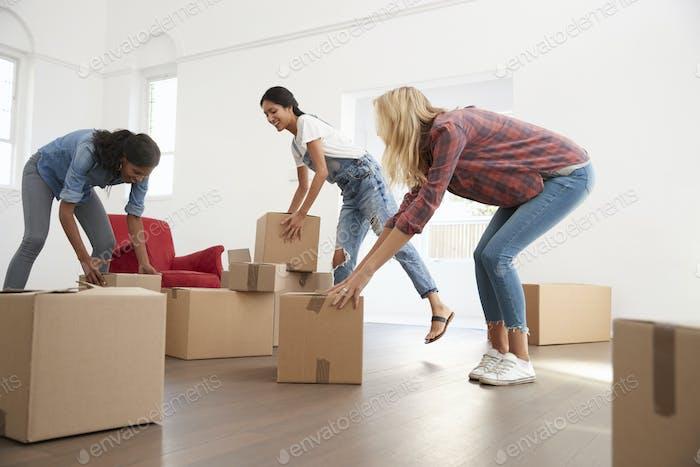 Drei weibliche Freunde tragen Boxen in neues Zuhause auf Umzug Tag