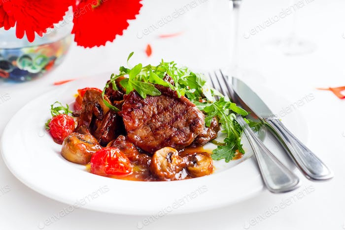 Juicy steak medium rare beef with spices and grilled vegetables.