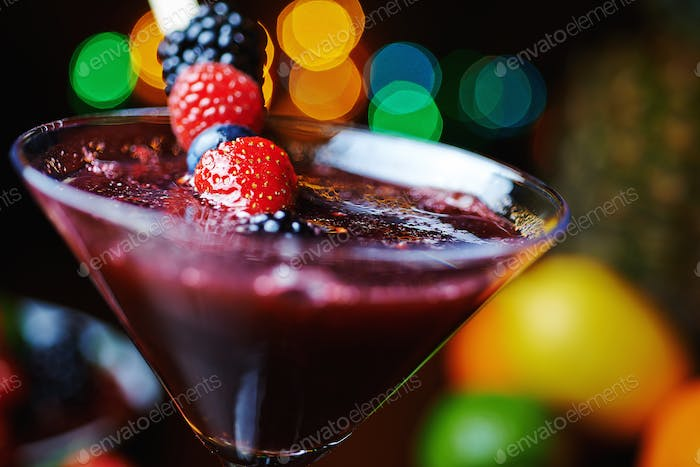 close up glass of tropical cocktail with berries or lemonade.