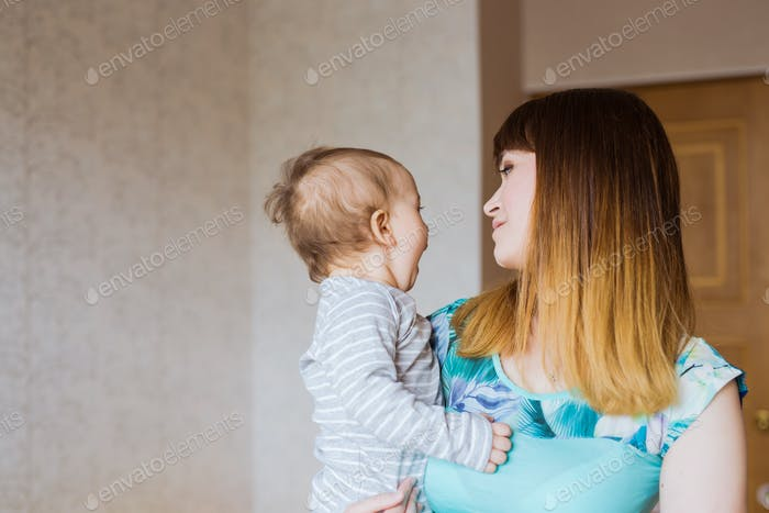 Happy mother with adorable baby boy indoors