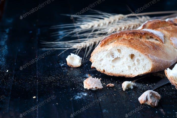 bread with wheat ears on dark board
