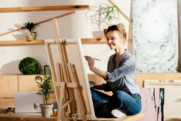 улыбающаяся художница сидит на столе и рисует на холсте в студии