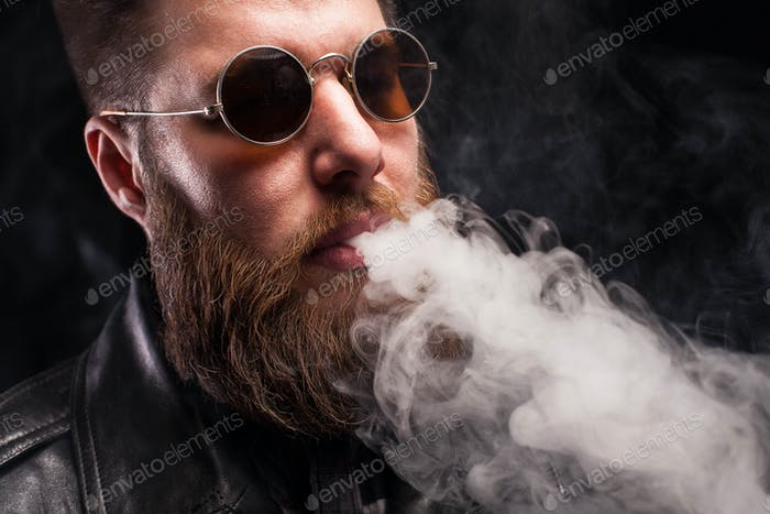Bearded man in leather jacket and brown sunglasses over black background