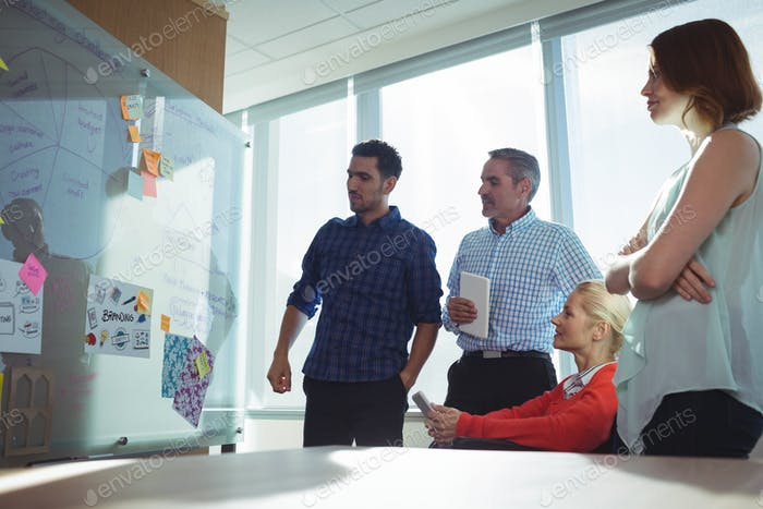Thoughtful business colleagues looking at whiteboard in office