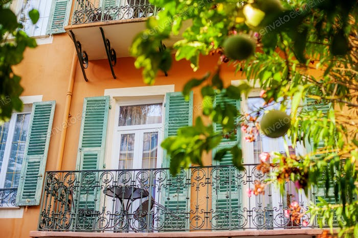 Balcony with decorative wrought-iron railings, table and open shutters