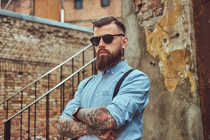 Old-fashioned tattooed man in a shirt with suspenders, standing near an old building outdoors.