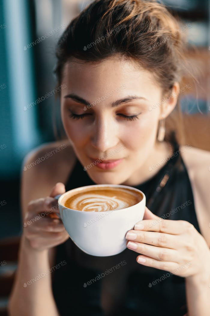 Refined Woman Enjoying Cappuccino or Latte on a vibrant, colorful background indoors.