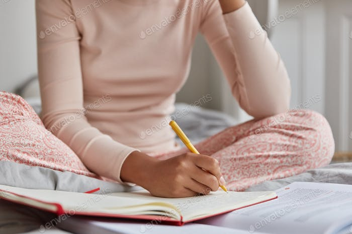 Unrecognizable woman dressed in casual nightwear, writes in notebook, has inspiration for studying.