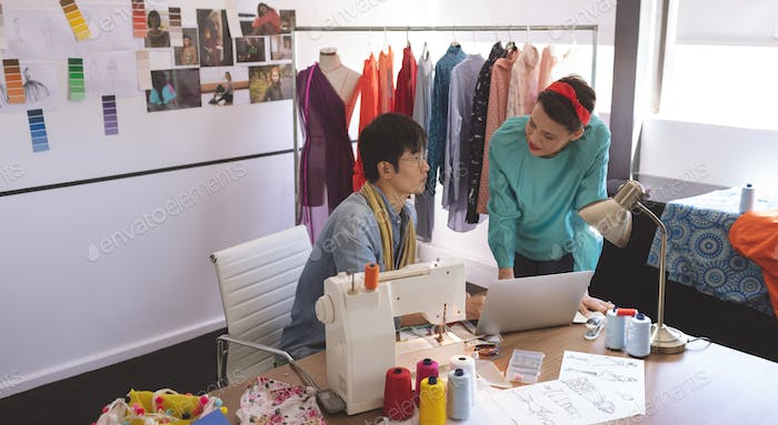 Front view of Multi-ethnic fashion designers discussing over laptop at desk in design studio