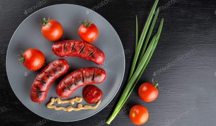 Fried sausages on a plate with tomatoes and ketchup