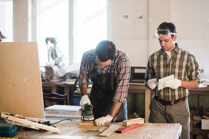 two man polishes boards. carpenter with a sander