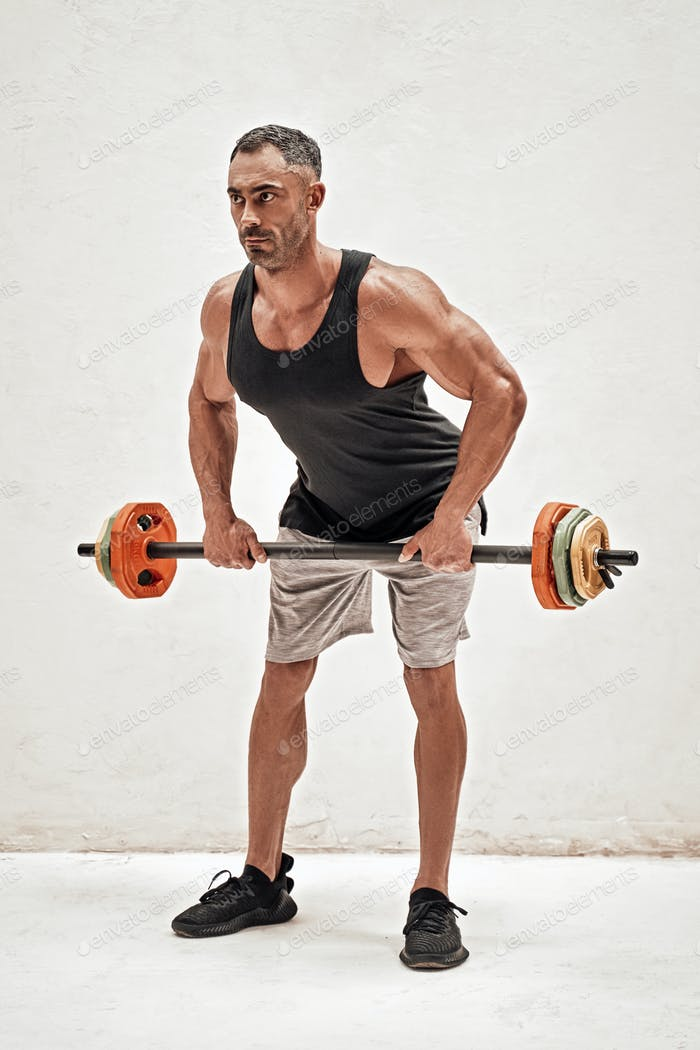 Athletic man isolated on a white background doing and exercise with a barbell