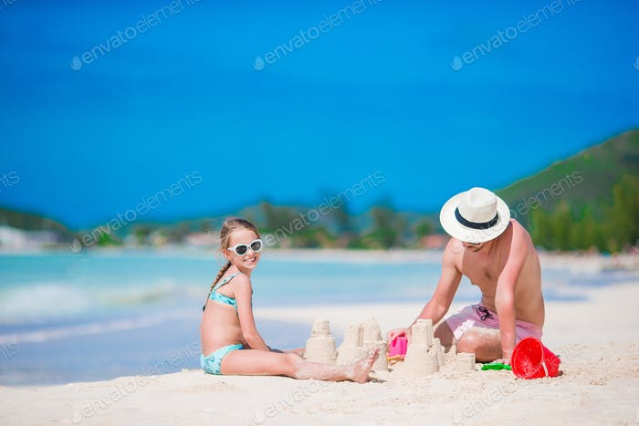 Family making sand castle at tropical white beach. Father and girl playing with sand on tropical