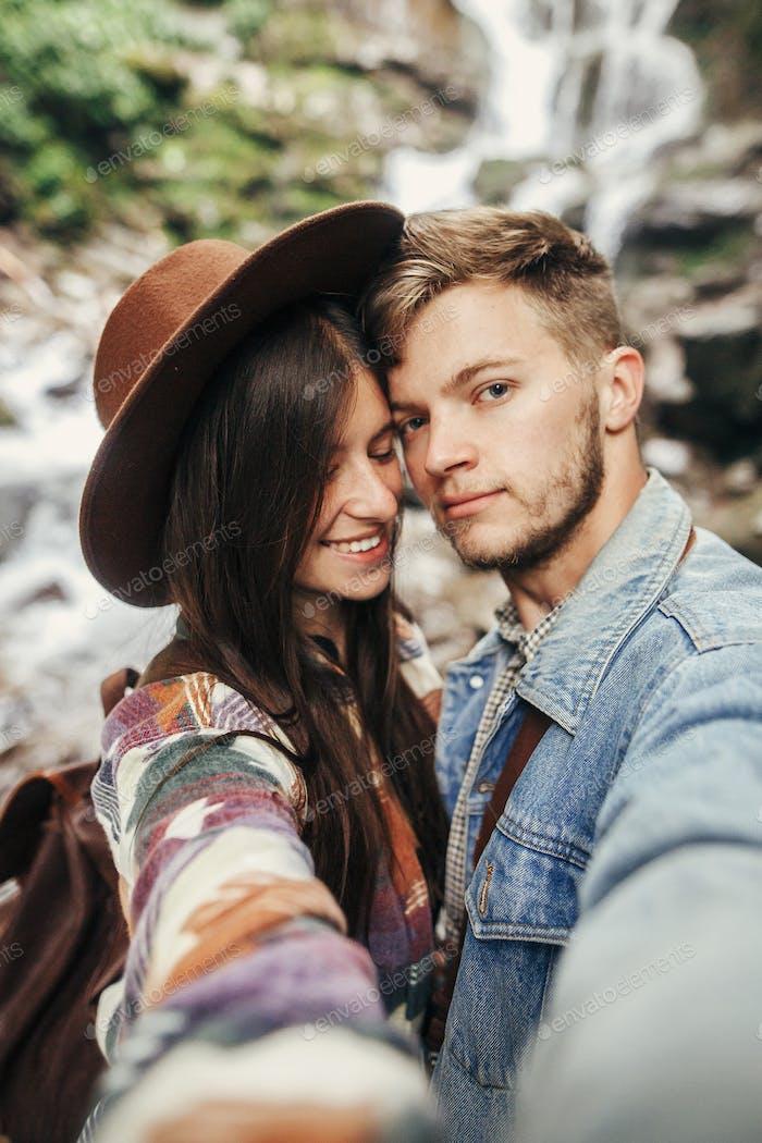 stilvolles Hipster Paar nehmen Selfie und küssen am Wasserfall im Wald in den Bergen
