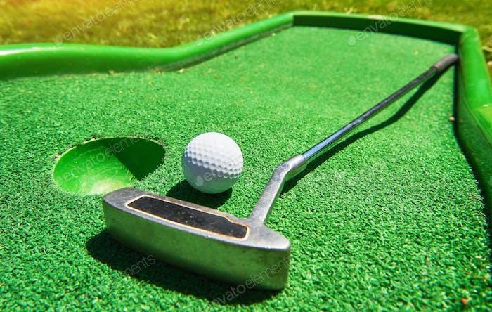 Golf ball and Golf Club on Artificial Grass