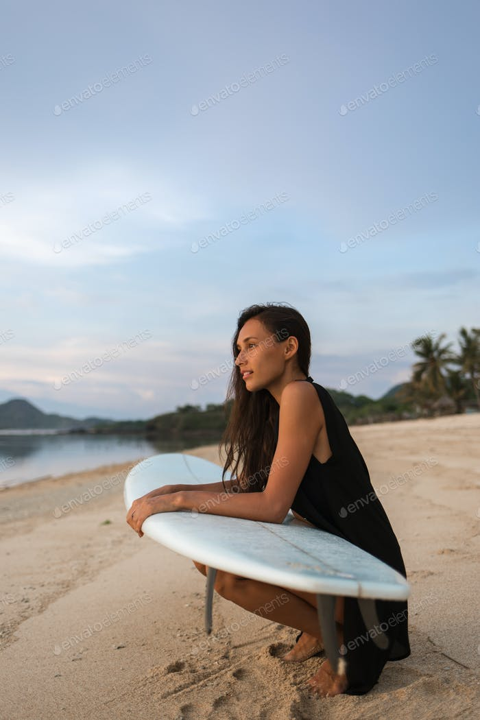 sun-tanned brunette attractive girl or woman (tourist, surfer)