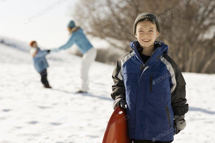 Ein Junge, der einen Schlitten im Schnee hält, und eine Mutter und ein Kind hinter sich.