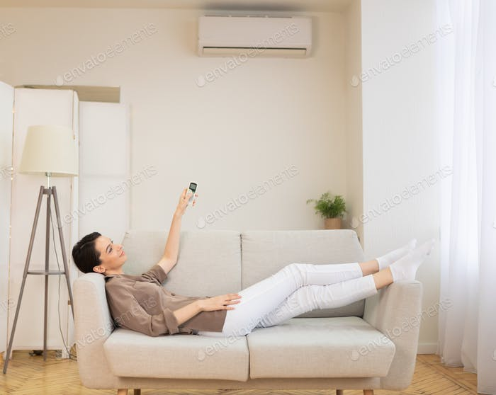Thumbnail for Young woman switching on air conditioning at her house